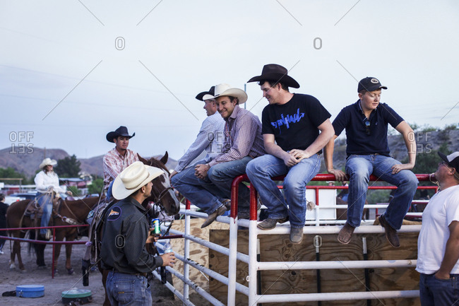 New Mexico, USA - May 11, 2013: Cowboys sitting on cattle-pen fence in Truth or Consequences, New Mexico, USA