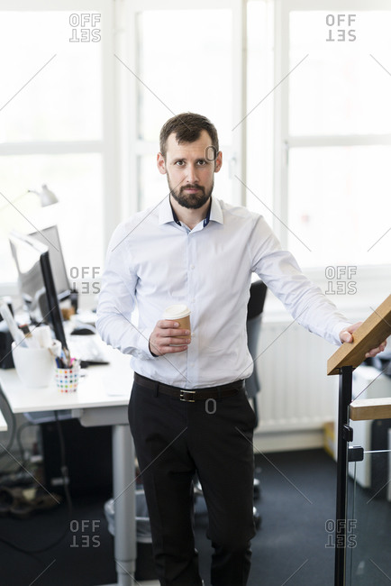 Businessman holding a coffee at office