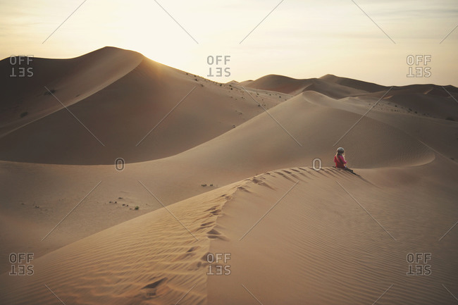 Girl sitting on the ridge of a desert dune in the distance