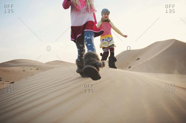 Children running in desert wearing furry boots