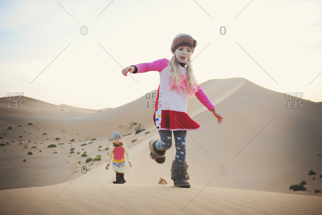Girl running in desert wearing furry boots