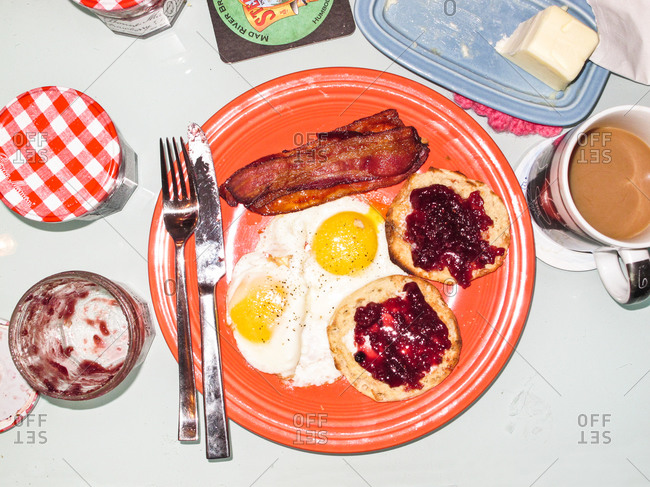 Hearty breakfast with bacon, eggs, and English muffins with jam