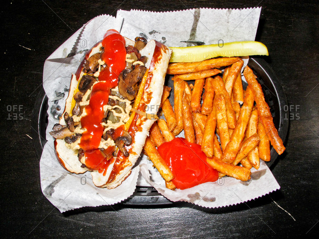 Bratwurst with fries and a pickle