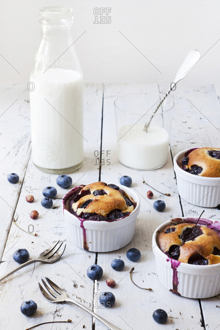 Three French clafoutis with blueberries and cherries in ceramic ramekins with a milk glass bottle and milk in glass with spoon