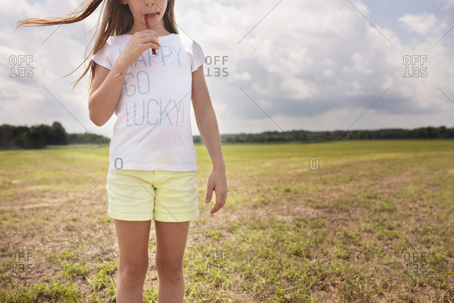 Girl eating twizzler in open field