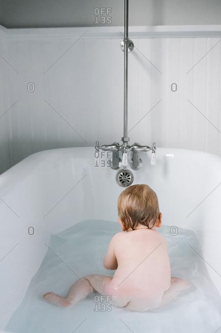 Baby sitting in the bathtub
