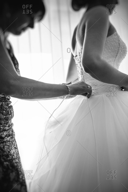 Mother helping daughter with wedding dress