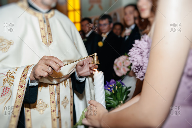 Priest extinguishing wedding candle