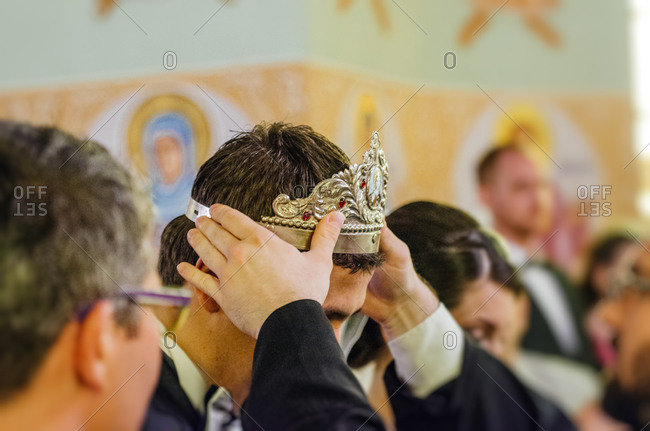 The crown is placed on the groom's head