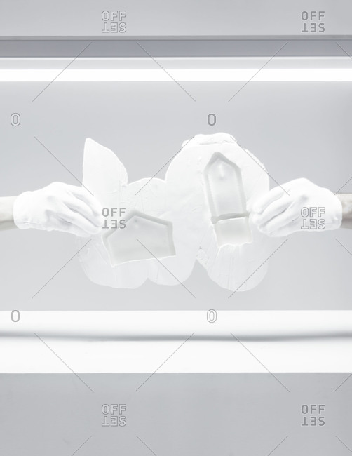 Gloved hands holding a mold