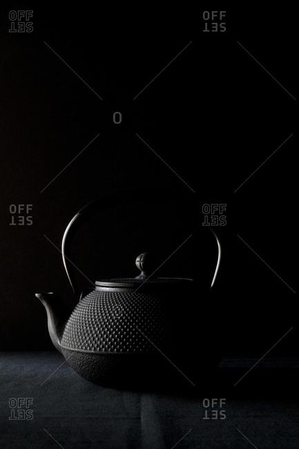 Black teapot on black background