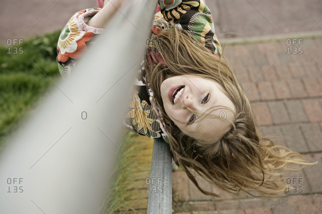 Happy young girl hanging upside down on a railing of a stairway