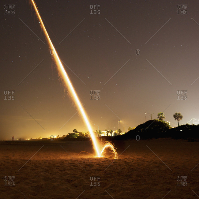 A firework exploding on a beach at night