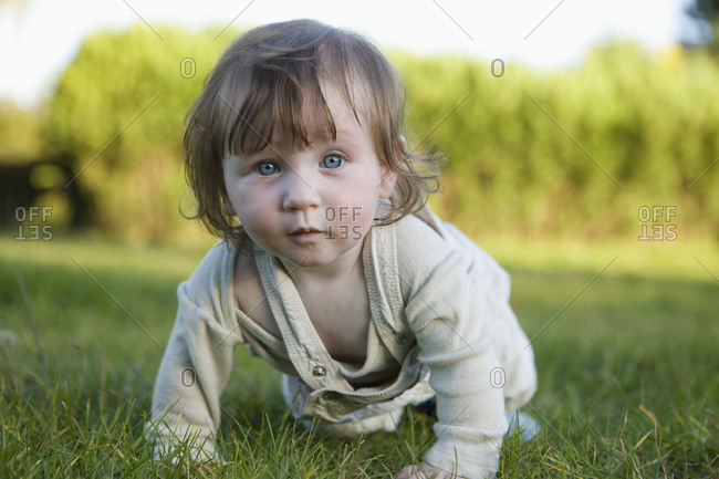 Baby girl crawling in grass