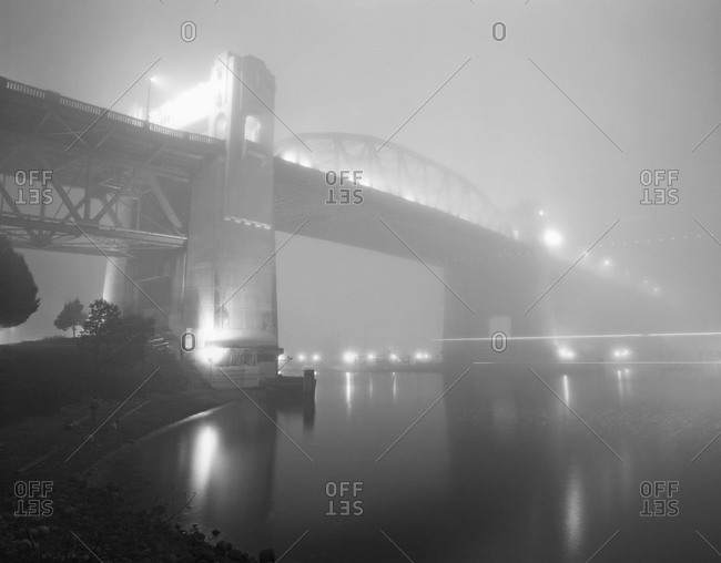 View of bridge covered with fog at twilight