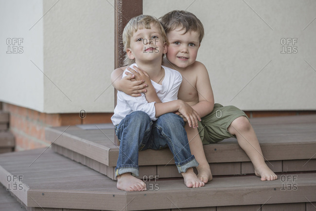Full length portrait of boys sitting arm around on porch