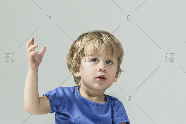Cute baby boy looking up with hand raised over gray background
