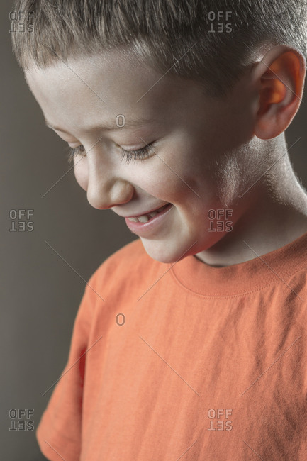 Close-up portrait of cute boy over colored background