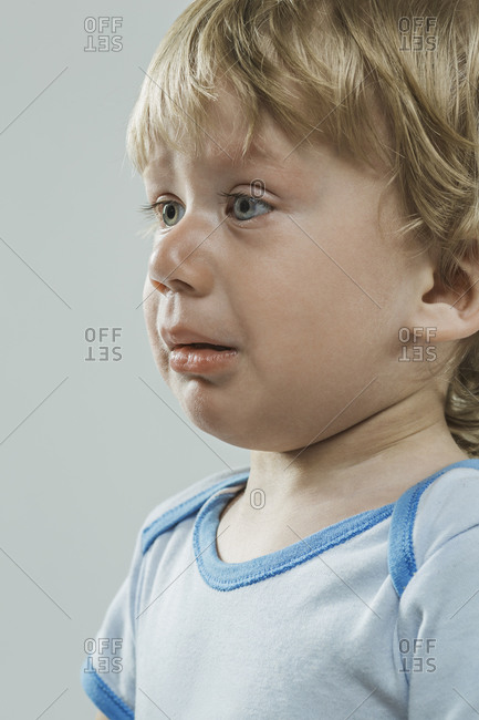 Cute boy crying over gray background