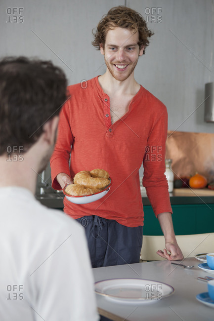 Smiling gay man holding croissants in plate looking at partner at home