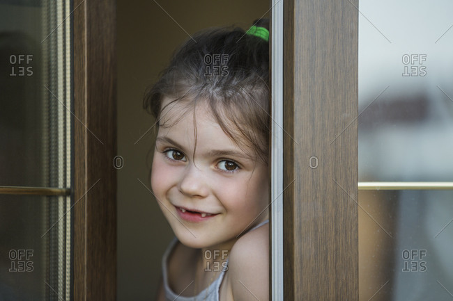 Close-up portrait of girl at doorway