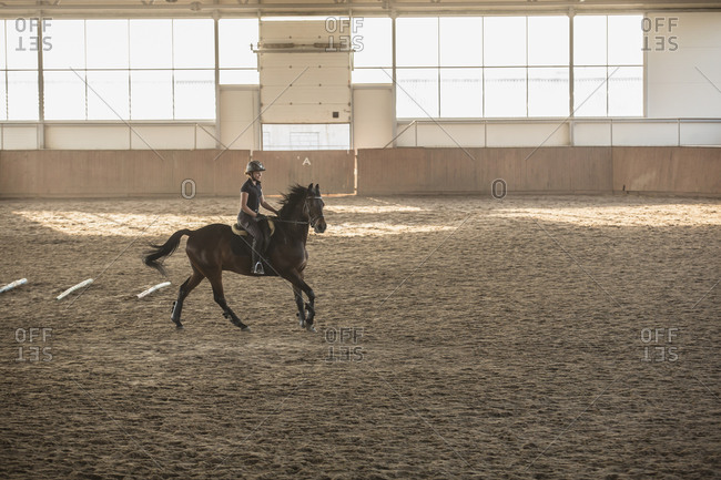 Woman riding horse in training stable