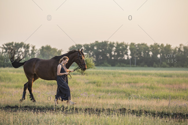 Mid adult woman with horse walking on field
