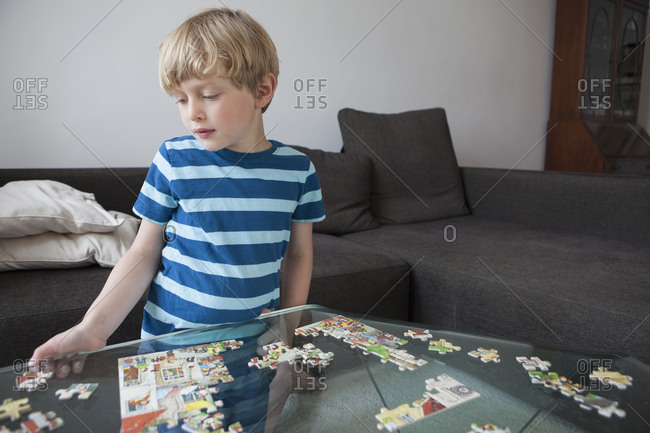Boy solving jigsaw puzzle on glass table in living room at home