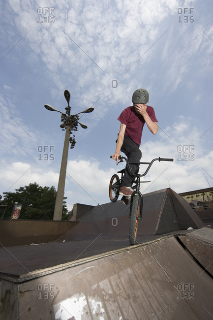 A young man balancing on a BMX bike at the top of a ramp