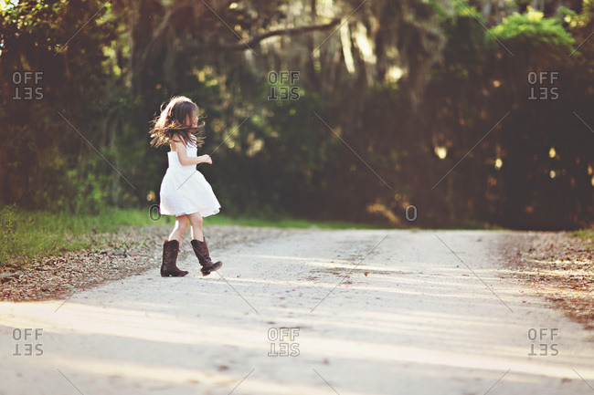 Young girl walking across country road in dress and boots