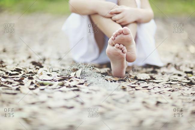 Girl sitting on dry leaves