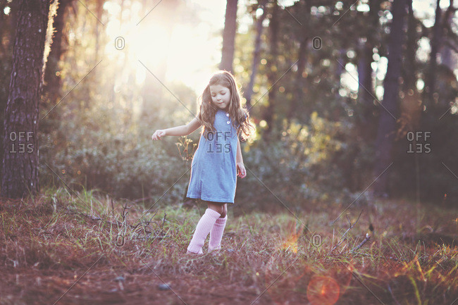 Young girl standing quietly in sun dappled countryside