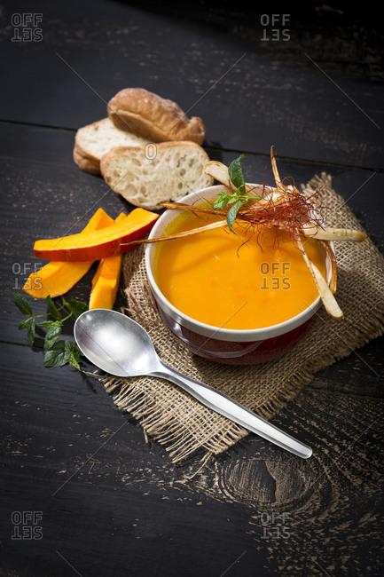Garnished bowl of hokkaido-soup on jute and dark wood