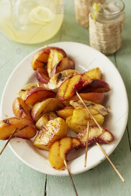 Grilled fruit skewers on a platter