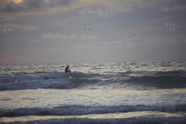 Person surfing in the evening