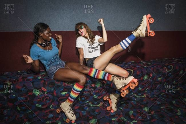 Young women posing on a bench at a roller skate rink