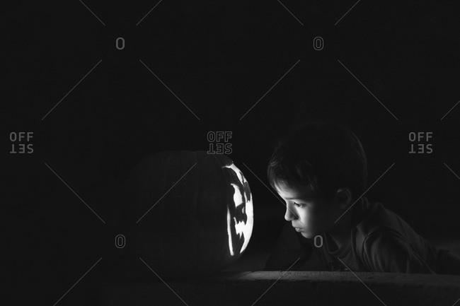 Young boy looking at a Jack-o'-lantern