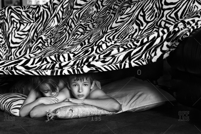 Brothers lying under a bed