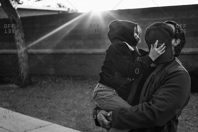 Boy covering his father's face with a cap