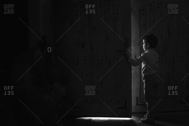 Young boy opening a door