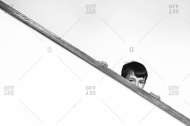 Boy hiding behind the railing of a staircase