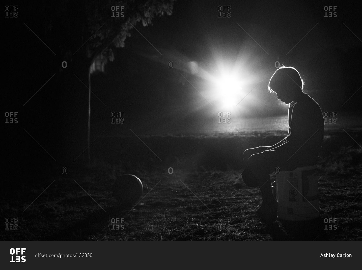Lonely boy sitting in a park at night stock photo offset