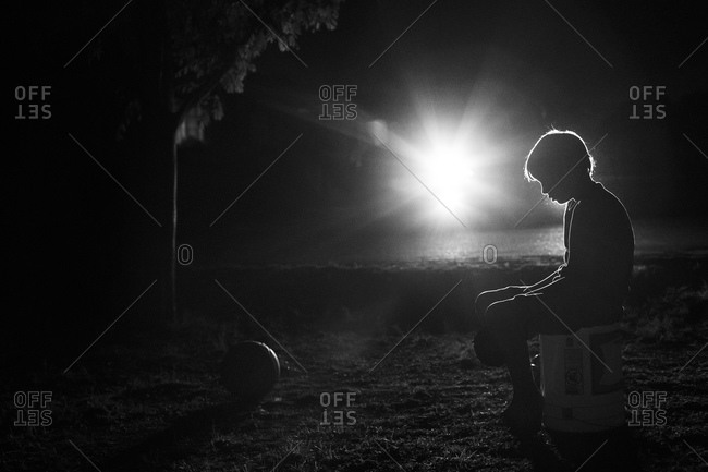 Lonely boy sitting in a park at night
