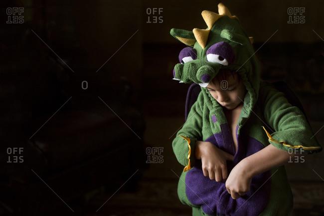 Boy putting on a dragon costume