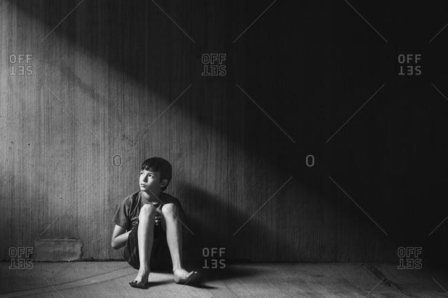 Boy sitting in an empty building