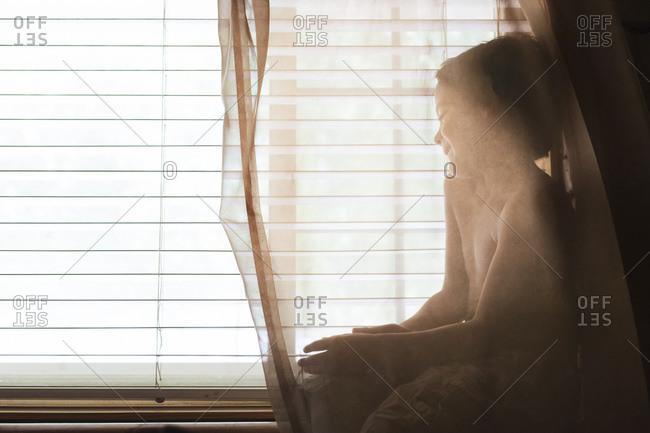 Boy hiding behind curtains