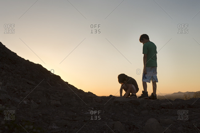 Children hiking on a hill at sunset