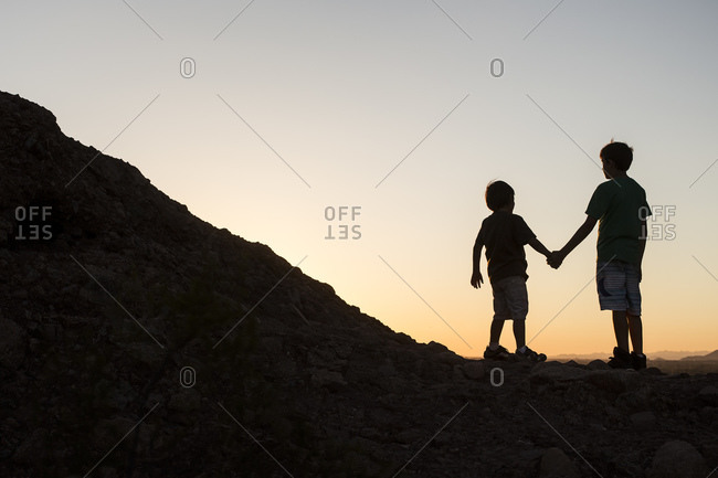Silhouette of little boys hand in hand