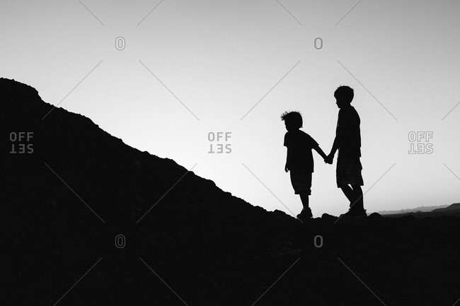 Silhouette of little boys standing hand in hand