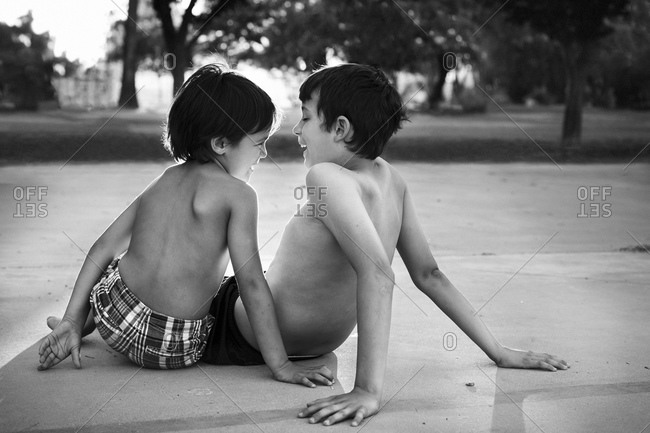 Boys having conversation while sitting on the ground